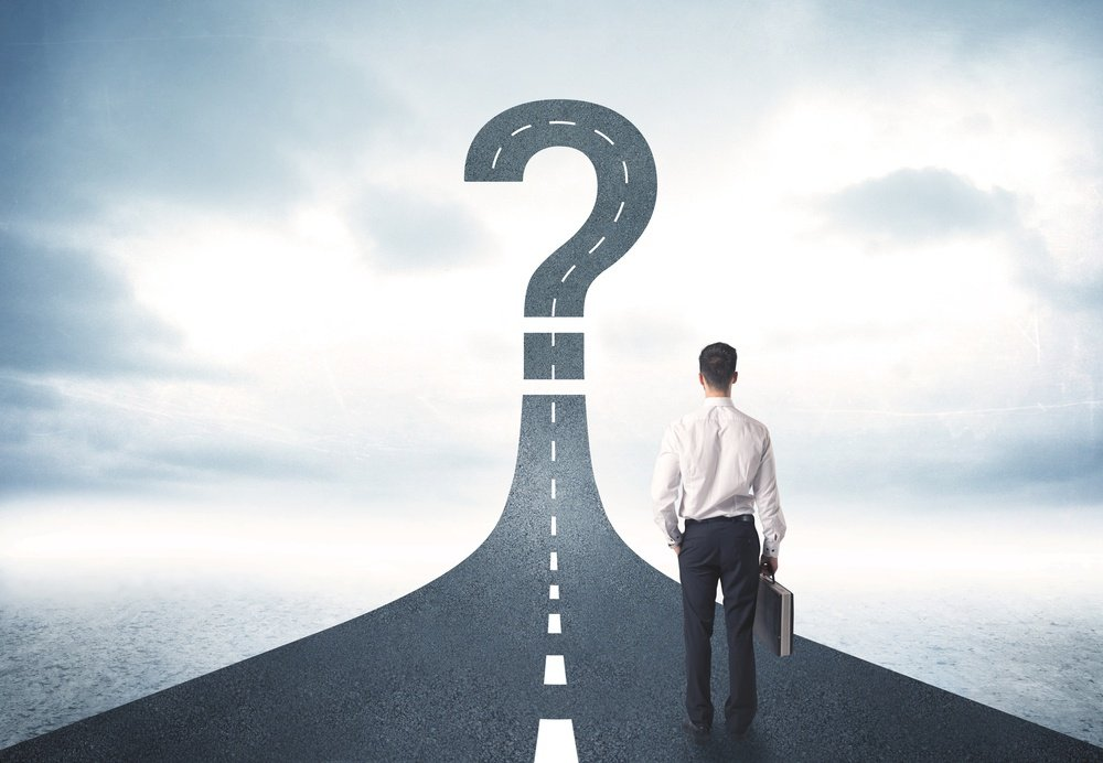 Business person looking at road with question mark sign concept