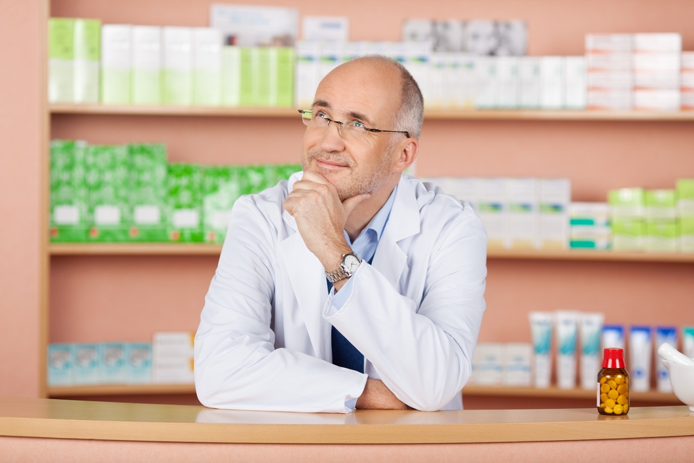 Close up portrait of looking up pharmacist standing in pharmacy drugstore