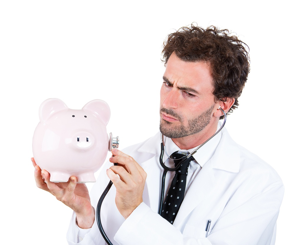 Closeup portrait, young curious male man healthcare professional, doctor, nurse listening to piggy bank with stethoscope. Medical insurance, medicare reimbursement concept . Health-law coverage gap