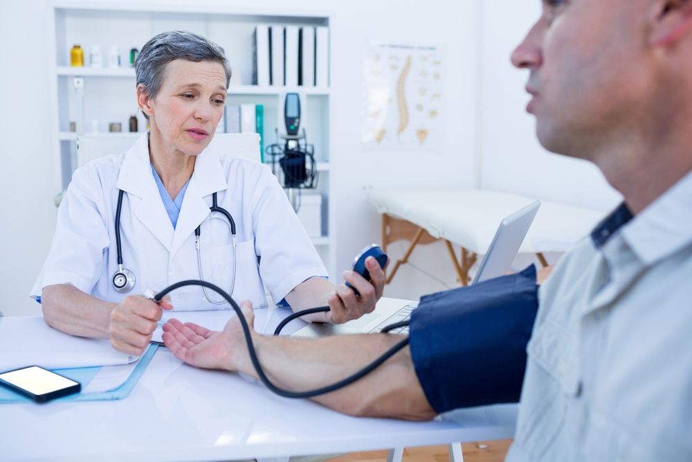 Doctor checking blood pressure of her patient in medical office