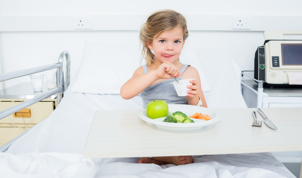 Portrait of little sick girl eating healthy food in hospital bed