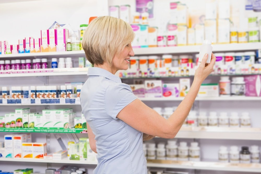 Pretty blonde customer looking at medicine in the pharmacy