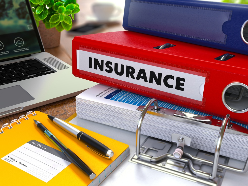 Red Ring Binder with Inscription Insurance on Background of Working Table with Office Supplies, Laptop, Reports. Toned Illustration. Business Concept on Blurred Background.