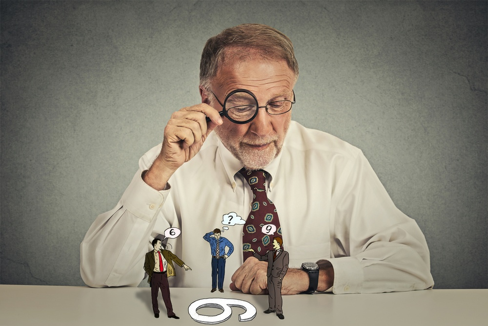 Senior business man with glasses sitting at desk skeptically looking at group arguing people through magnifying glass isolated grey wall background. Human expression, attitude. To each its own concept