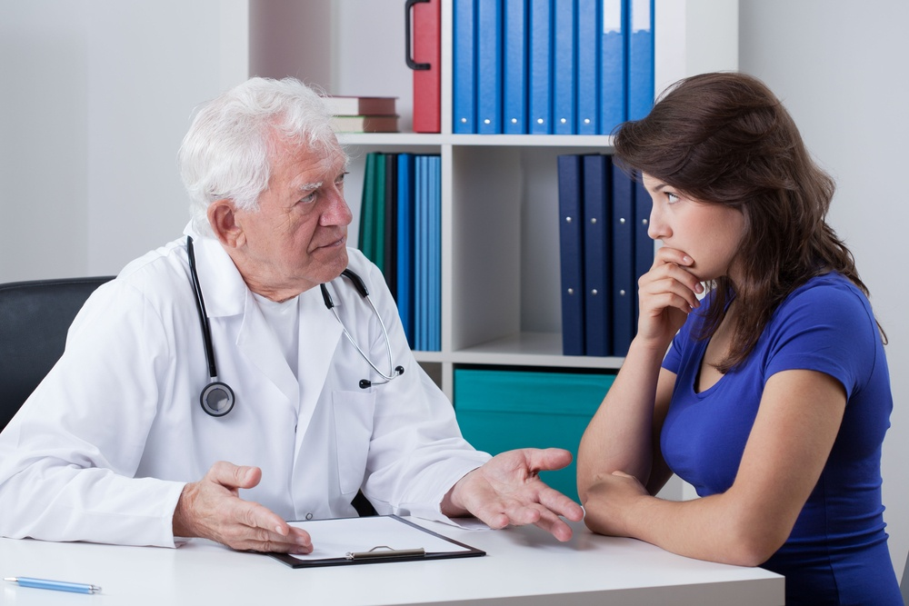 Senior male doctor talking with worried patient