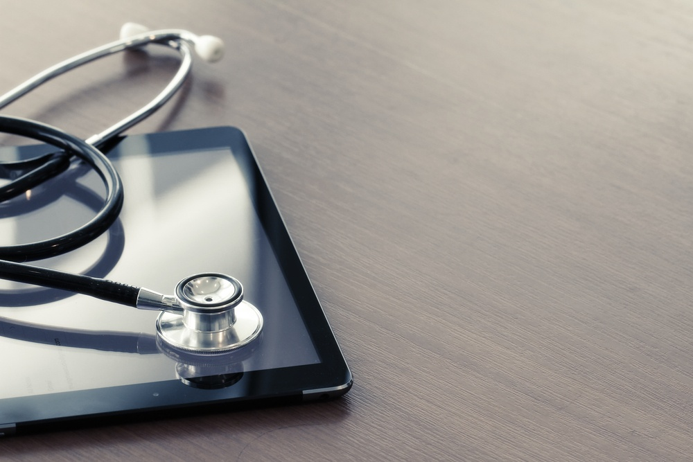 Studio macro of a stethoscope and digital tablet with shallow DOF evenly matched abstract on wood table background copy space-1