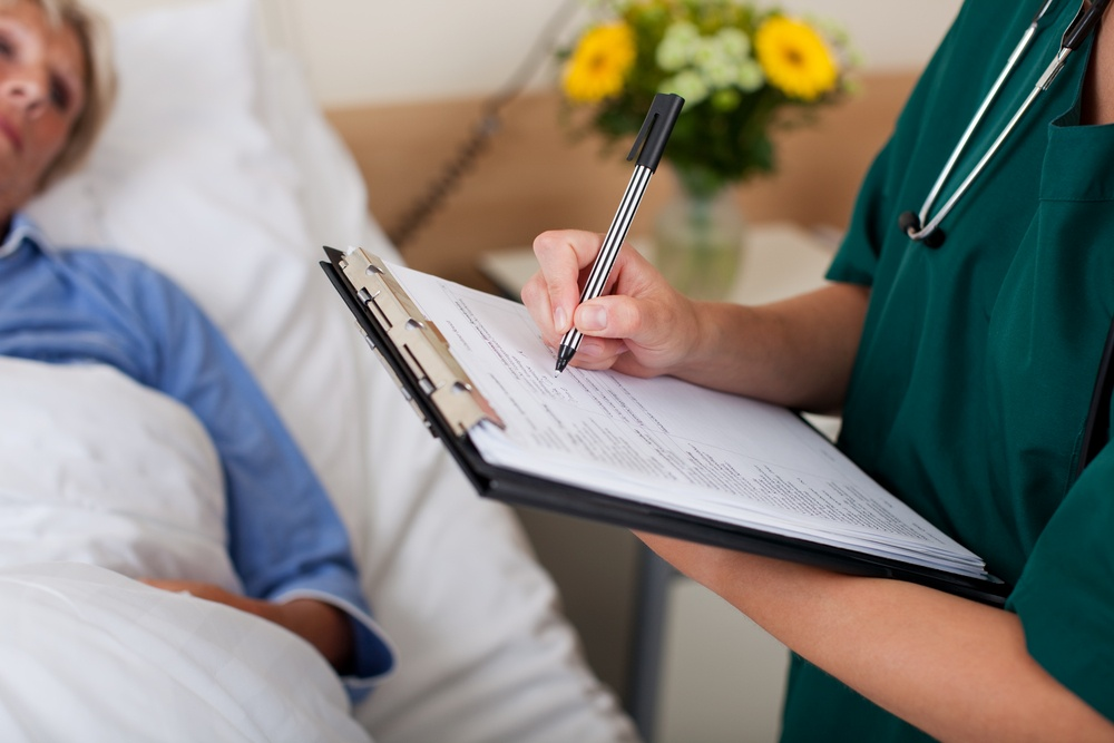Writing on clipboard with patient in background in hospital
